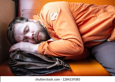 young passenger of an electric train sleeps on a bench, putting a briefcase under his head