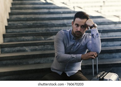 Young passenger sitting on stairs and waiting train to come