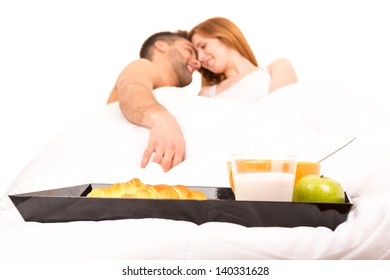 Young passionate couple having breakfast in bed