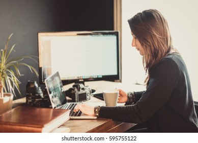 Young passionate woman photographer editing pictures in a photographic studio