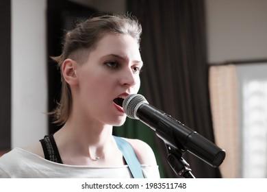 junge leidenschaftliche Frau, die in einem Studio in einem Mikrofon singt. Tonträgeraufnahme. professioneller Sänger.