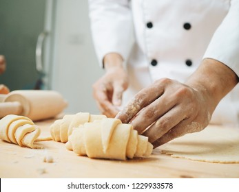 Young pastry chef making some croissant in the bakery.