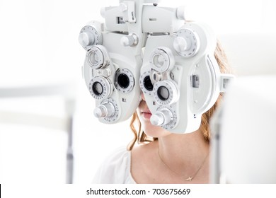Young patient eye examination at optometrist using phoropter