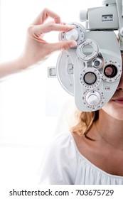 Young patient eye examination at optometrist using phoropter