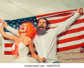 young patriotic happy couple of bearded man with blue beard and pretty woman with red hair in white dress with american flag outdoor celebrating independence day usa