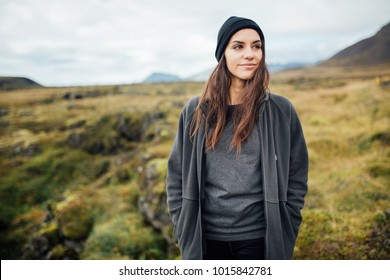 Young peaceful woman enjoying view of the moss covered meadows in Iceland.Arctic circle wild nature.People and nature connection.Female wearing comfortable camping/hiking clothes.Traveling and camping