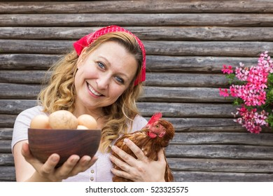 Young peasant woman in front of a wooden background with eggs and a hen