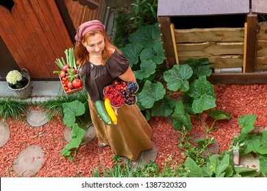 Young peasant woman in the garden carries bowls with fruits and vegetables