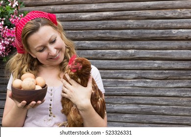A young peasant woman holding a bowl of eggs and a hen