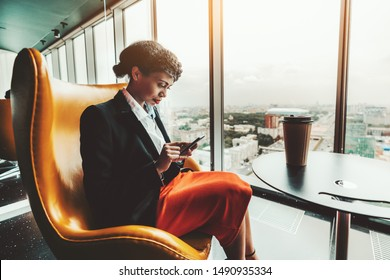 A young pensive African-American woman entrepreneur is reading a message on the screen of her cellphone while sitting on a curved yellow armchair near the window of a top business skyscraper