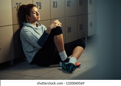 Young pensive athletic woman sitting in locker room and has no will for exercising.
