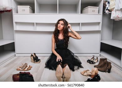 Young pensive beautiful brunette girl choosing shoes in her wardrobe sitting on the floor. She is dressed in a black outfit, surrounded by clothes and shoes.