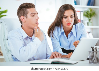 Young pensive businessman and businesswoman talking and working on laptop in the office.
