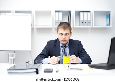 Young pensive businessman at his workplace in bright office