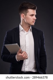 Young Pensive Businessman With Tablet Computer