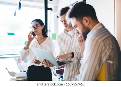 Young and pensive coworkers standing in corridor and discussing new business project using laptop while beautiful female colleague in glasses talking on smartphone