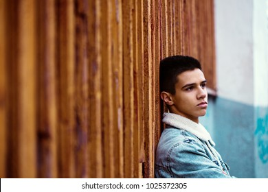 Young pensive guy on the background of an old wooden wall