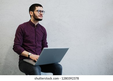 Young pensive guy using laptop, wearing glasses on background of white.