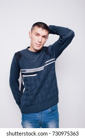 young pensive man brunette with short hair. street style:blue jeans and a warm winter sweater. posing in Studio on a white textured background. emotional portrait
