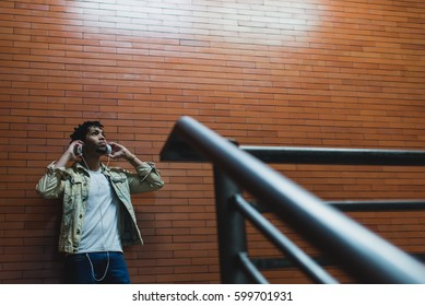 Young pensive man putting headphones standing near the brick wall.