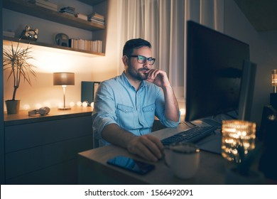 Young pensive man working remotely from home at night.