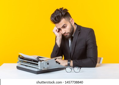 Young pensive tired business man or manager types a document on a typewriter on a yellow background. Office concept and documentation.