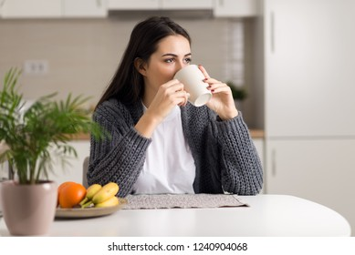 Young pensive woman having her coffee at dining table
