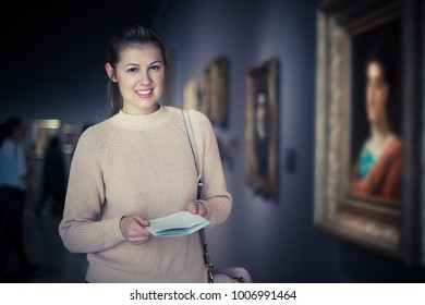 Young pensive woman visitor with guide book looking at exposition in art museum