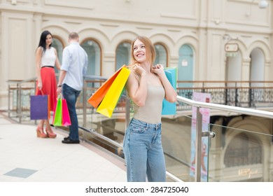 Young people with a lot of bags from the fancy shops. Shopping, sale, gifts and holidays concepts. High-street shopping.