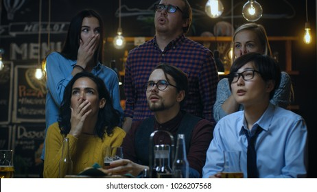 Young People in the Bar Watch TV Suddenly Breaking News Show that Tragic Events Unfold. Young People Are Horrified, Saddened and Shocked.