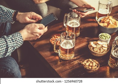 Young people at a beer party using mobile phones , wifi party toned,