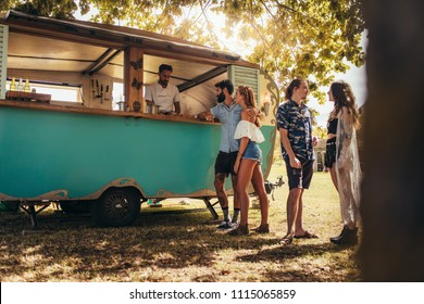 Young people buying street food from a food truck at park. Group of men and woman at food truck.