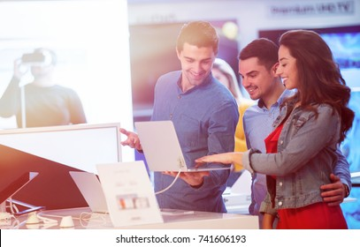 young people buying and testing latest laptop