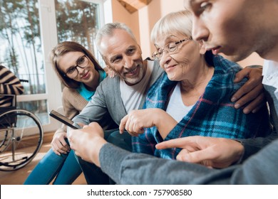 Young people came to visit the older man and woman in a nursing home. They show something on the tablet. Older people are happy with what they see. In the back, other old people play chess.