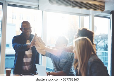 Young people in casual clothes giving high fives to each other as if celebrating something, against bright window in cafe or business office