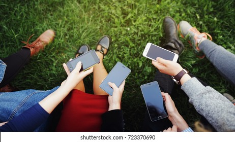 Young people in casual clothes holding cell mobile phones and exchanging cryptocurrency with each other online in real time in the street. Blank dark screens, for use as a template