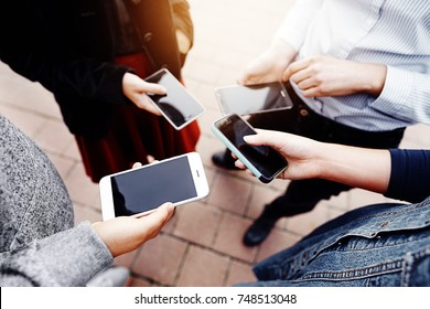 Young people in casual clothes holding cell mobile phones in the street with blank screens. Can be used as template for cryptocurrency transactions visible on the screens