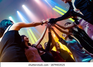 Young people celebrating a party, drink and dance . Group of friend toasting drinks while having fun at the disco club at night . Friendship and nightlife concept .