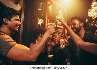 Young people celebrating and toasting drinks at nightclub. Friends having good time at club.