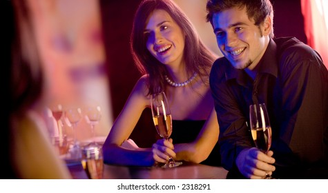 Young people with champagne glasses in restaurant, meeting