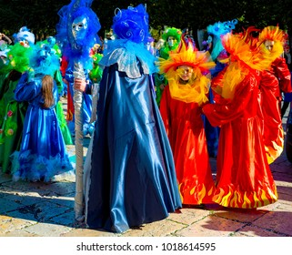 Young people and children with beautiful and colorful clothes during the parade of masked groups in the city streets of a city in Puglia. Italy