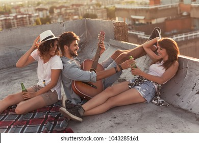 Young people chilling out and partying on a building rooftop, playing the guitar and drinking beer