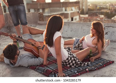 Young people chilling out and partying at a building rooftop. Focus on the girl on the right