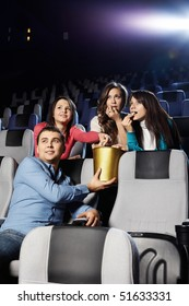 Young people at cinema eat pop-corn