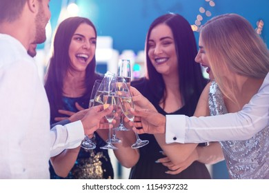 Young people clinking glasses with champagne at birthday party in club