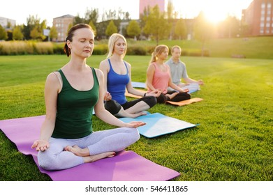 young people in colored clothes doing yoga on fresh grass