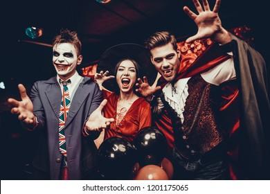 Junge Leute in Kostümen feiern Halloween. Gruppe der jungen glücklichen Freunde, die Halloween-Kostüme tragen, die Spaß auf Party in der Nightclub, indem sie schändliche Gesichter zu tun. Halloween-Feier