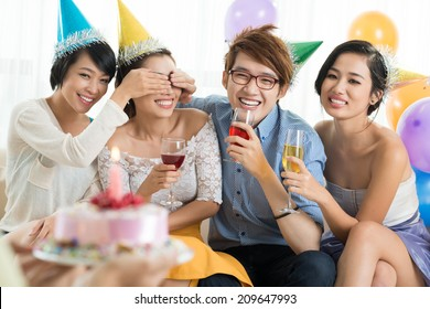 Young people covering eyes of their friend to give her a birthday cake