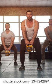 Young People in Crossfit Gym Training With Kettlebells. Small Group of Male Athletes During Workout. Sports, Fitness, Healthy Lifestyle and Teamwork