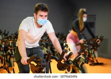 Young People cycling in the fitness gym with protective face mask during coronavirus outbreak . High quality photo